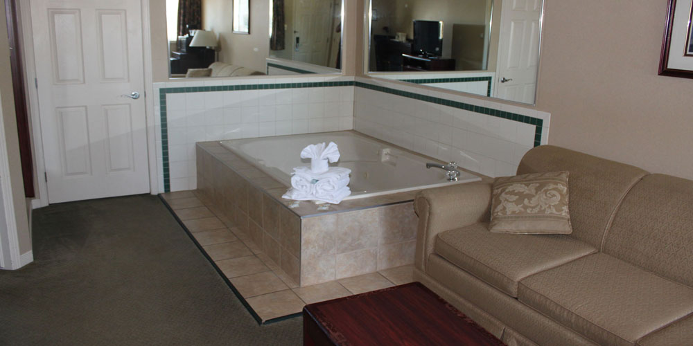 open bath tub with a tan sofa in the seating area & fresh white towels