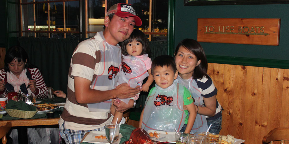 young family wearing lobster bibs posing for a picture at The Lobster Trap