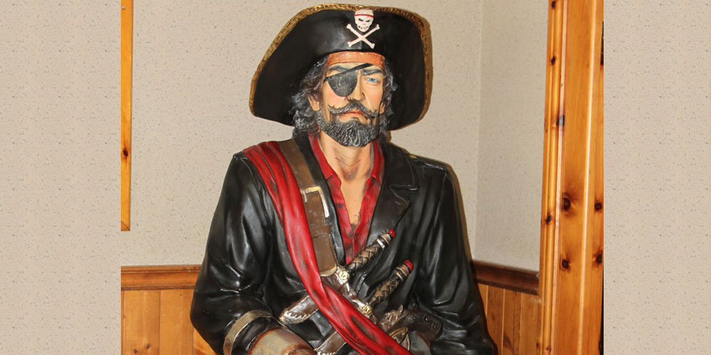 statue of a pirate, skull hat, red under shirt, black jacket with brown belt