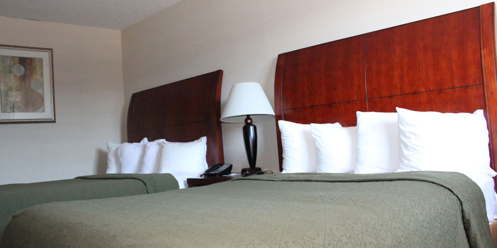 two beds in a room with a long oak head board on each and green covers